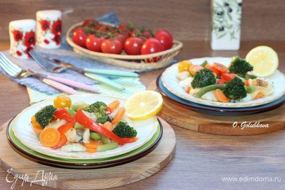 Раскладываем овощи с рыбой по тарелкам. Сбрызгиваем блюдо лимонным соком, оливковым маслом, солим и перчим.