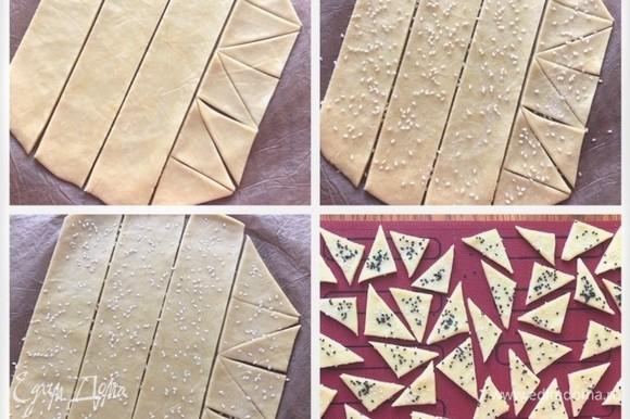 Остатки теста можно использовать в качестве декора. Собираем в комок и раскатываем между двух листов пекарской бумаги без заломов. Вырезаем печеньки треугольные, посыпаем крупной солью и кунжутом и проходимся скалкой, чтобы посыпку придавить и переложить печеньки на перфорированный коврик. Можно посыпать пармезаном, травками. Отправляем в холод/мороз. Затем печем до готовности.