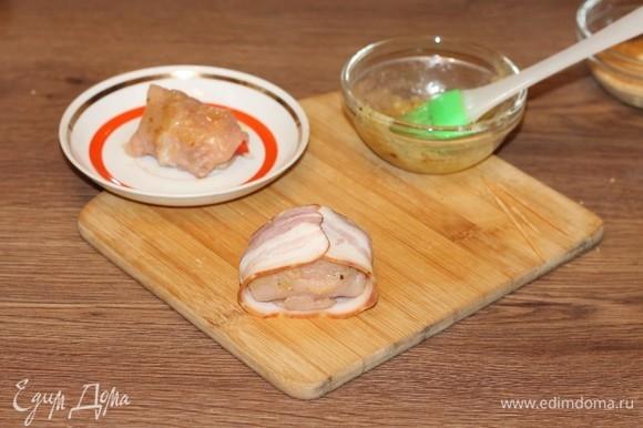 Смажьте куриные рулетики масляной смесью и заверните в полоску бекона с одной стороны.