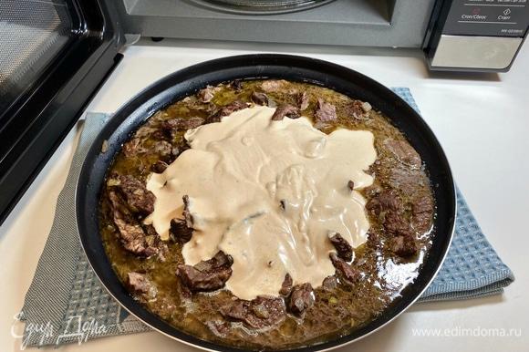 Сметанный соус вылить к мясу, перемешать.