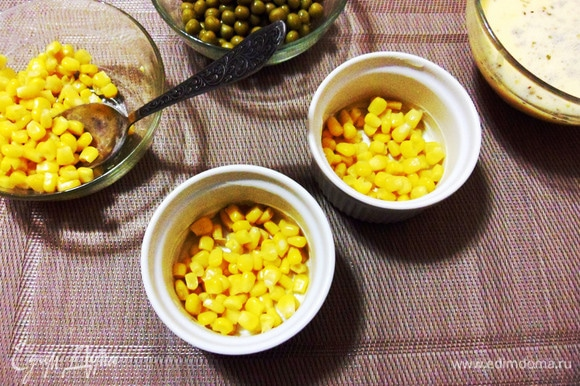 Смазать керамические формочки небольшим количеством оливкового масла и выложить по столовой ложке консервированной кукурузы в каждую.