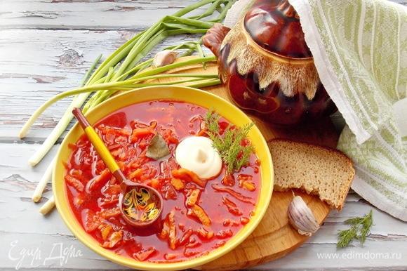 Достаем горшочек, разливаем по тарелкам суп и подаем со сметаной, зеленью, луком и чесноком.