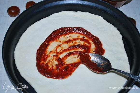 Емкость для микроволновой печи смазала оливковым маслом. Тесто разделила на две части (из этого количества теста и продуктов получилось 2 пиццы). Раскатала тонко тесто, смазала его томатным пюре со специями.