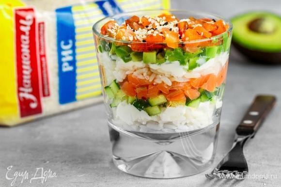 Укладываем слоями в стакан ингредиенты в следующем порядке: рис, творожный сыр, огурец, лосось, рис, творожный сыр, авокадо, лосось. Сверху посыпать белым и черным кунжутом. При подаче полить соевым соусом.