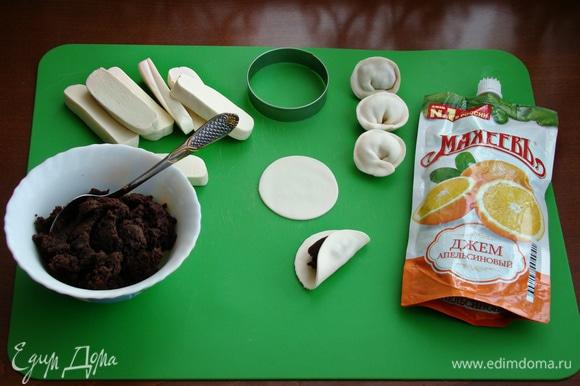 Остывшую шоколадную массу нарезать на порционные кусочки. Каждую часть размять руками (нагреть), тонко раскатать, вырезать кружочки и налепить пельмени. Готовые пельмени поставить в холодильник. Если шоколадная масса липнет, то стол можно слегка припылить кукурузным крахмалом.