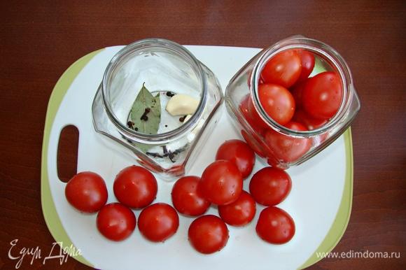 На дно банок уложить по лавровому листу, по паре зубчиков чеснока, перец горошком, гвоздику и плотно уложить в банки помидоры черри. Количество ингредиентов рассчитано на две банки объемом 0,7 л.