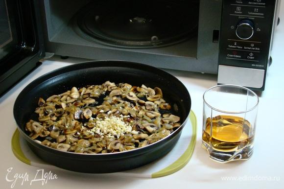 К обжаренным луку и грибам добавить измельченный чеснок и влить белое сухое вино. Перемешать и выпарить при средней мощности (600 Вт) в течение 5 минут.