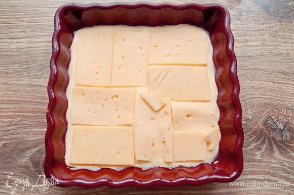 Форму 15х15 смазываем растительным маслом и выливаем 1/3 теста, разравниваем. Твердый сыр нарезаем тонкими полосками и раскладываем по всей поверхности теста.