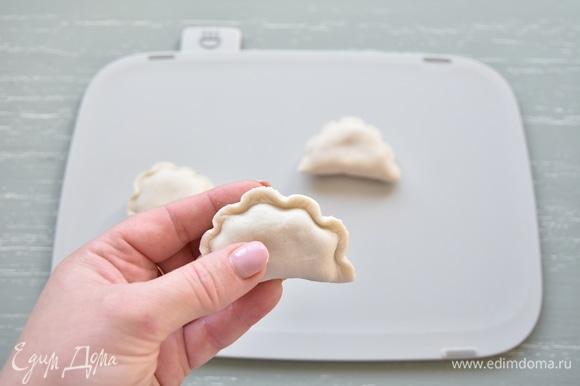 Для получения волнистого края вареника прижать край теста с помощью китайской деревянной палочки к основе вареника. Их можно сразу отварить или заморозить впрок.