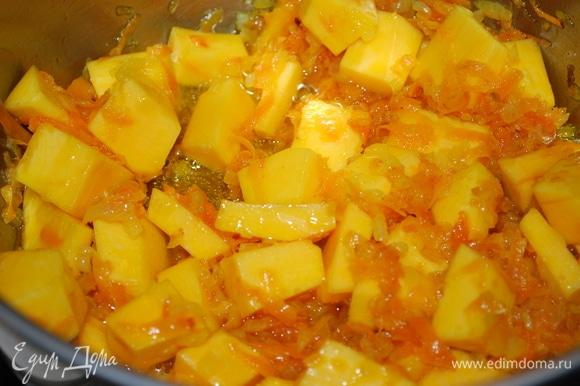 Тыкву нарежьте кубиками и добавьте в кастрюлю к моркови и луку.