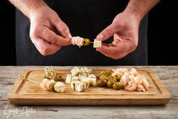 Сыр дорблю нарежьте кубиками (можно использовать любой другой мягкий сыр). Нанижите на шпажки сыр, маслины и креветки.