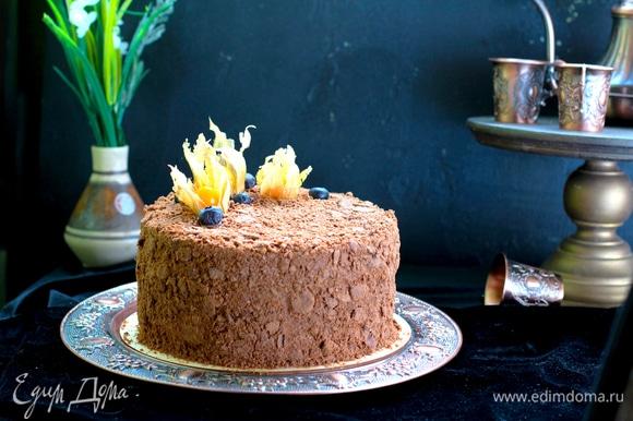 Собрать торт, обернуть ацетатной пленкой и затянуть в кольцо. Поставить груз и убрать на 1 час в холод. Покрыть торт остатками крема, посыпать толченой крошкой и снова убрать на 6–8 часов для пропитки.