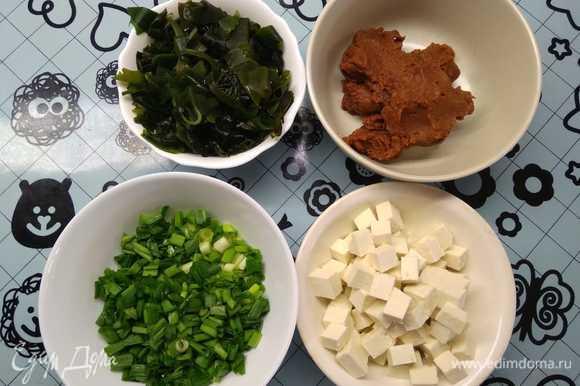 Подготовить ингредиенты: нарезать тофу на квадратики не более 1 см, нашинковать лук, подготовить мисо-пасту. Предварительно необходимо залить холодной водой сухие водоросли вакаме и оставить на 15 минут для набухания.