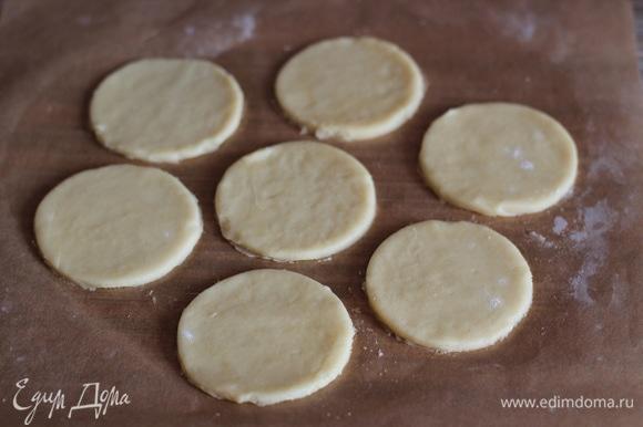 После охлаждения тесто раскатываем между двух листов пекарской бумаги, толщина печенья — 3–5 мм. Вырезаем формочкой или стаканом кружки. Размер — на ваше усмотрение, я делала крупненькие пирожные, диаметр круга у меня — 7 см.