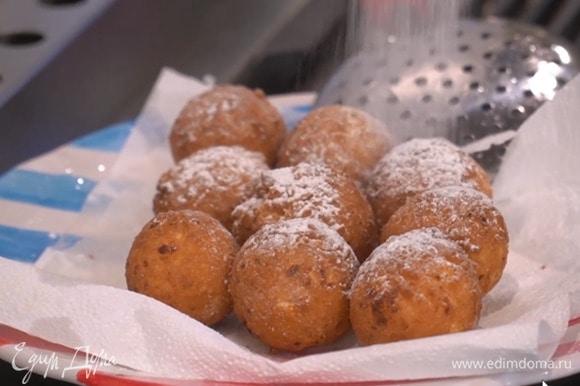 Горячие пончики посыпать сахарной пудрой.
