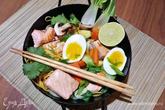 Теперь можно сервировать. Боулы традиционно подают в больших глубоких пиалах. Выложить лапшу с овощами, сверху — кусочки лосося, половинки яиц, затем посыпать свежей кинзой и зеленым луком. Добавить жареный арахис.