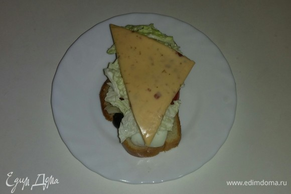 На каждый кусочек хлеба кладем треугольный кусочек сыра. Выкладываем все бутерброды на противень и ставим его в разогретую до 170°C духовку на 7–8 минут (время выпечки зависит от вашей духовки). Бутерброды готовы. Приятного аппетита!