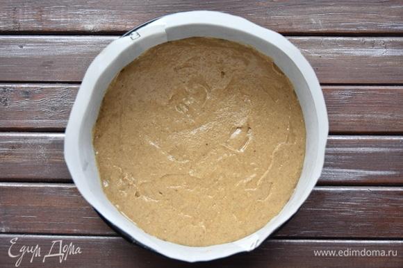 Форму для выпечки выстелить пергаментом, выложить тесто и разровнять.