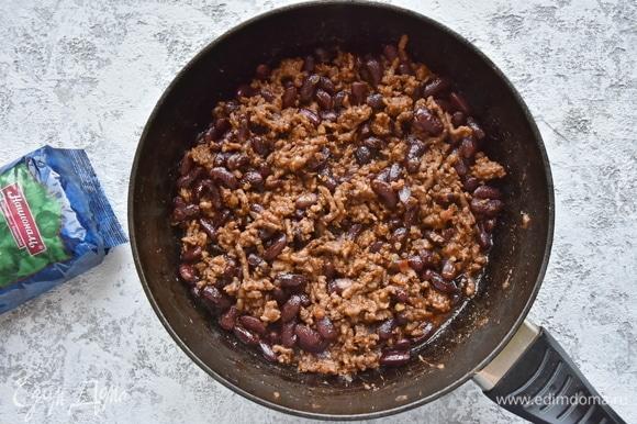 Фасоль замочить на ночь в воде. Промыть, залить чистой водой и отварить до готовности. В сковороде разогреть оливковое масло, выложить мелко нарезанный лук и чеснок. Всыпать тмин, паприку, кориандр, хлопья перца чили. Добавить говяжий фарш и обжарить. К обжаренному фаршу добавить томатную пасту, помидор, нарезанный кубиком, и отваренную фасоль, посолить. Влить немного отвара из-под фасоли (0,5 стакана) и потушить под закрытой крышкой до выпаривания лишней влаги.