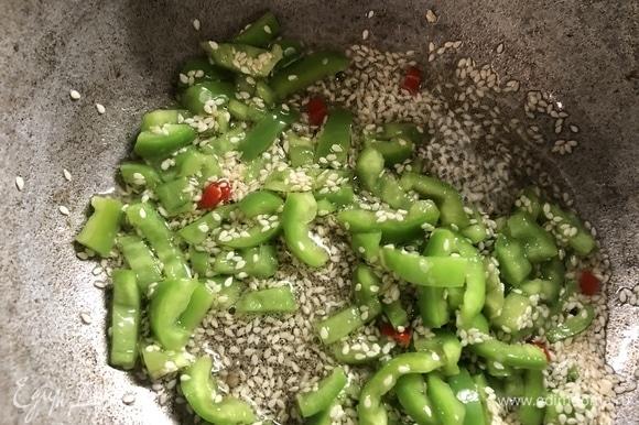 В казане с толстым дном нагреваем масло, добавляем перцы и кунжут, обжариваем.