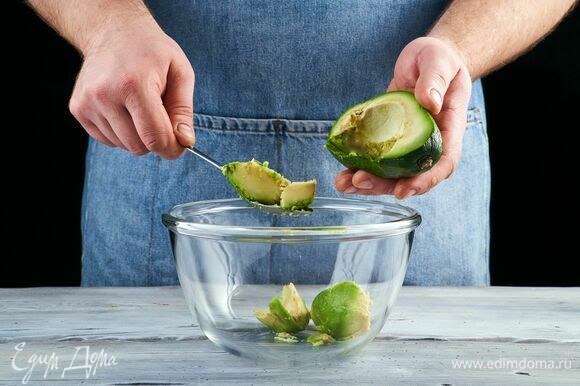 Авокадо разрежьте пополам, уберите косточку и вытащите ложкой мякоть.
