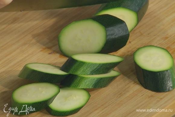 Цукини нарезать толстыми брусочками и выложить в форму к овощам.