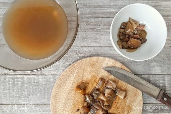 Сливаем через сито грибной бульон. Убираем специи, лук и чеснок. Крупные части грибов разрезаем, но не мелко. Бульон можно перелить обратно в кастрюлю и поставить на медленный огонь, чтобы бульон был горячим.
