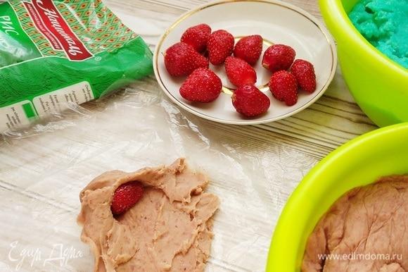 Из фасолевой пасты делаем лепешку. Удобнее раскатывать тесто в пищевой пленке. В серединку кладем клубничку и формируем шарик.