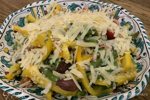 Готовый кускус и спаржу добавить в миску с овощами, полить все заправкой и перемешать, затем выложить на блюдо и посыпать натертым сыром.