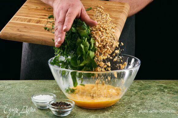 Добавьте в яйца рубленый грецкий орех и зелень.