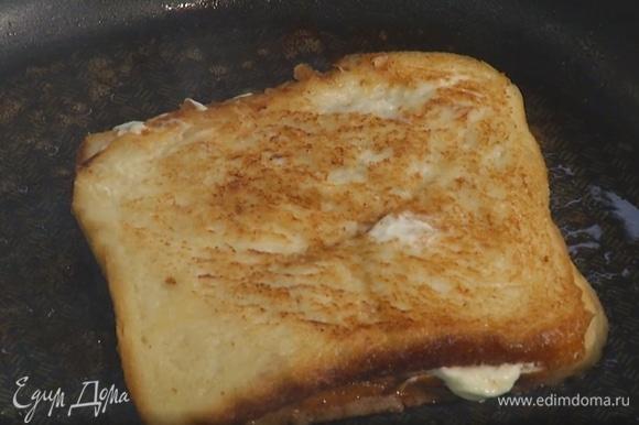 Разогреть в сковороде сливочное масло и слегка обжарить тост с двух сторон, перед подачей разрезать пополам.