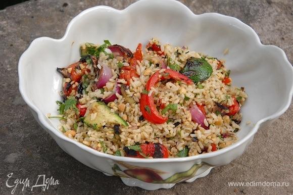 Обжаренные овощи выложить в глубокую миску и двумя ножами порезать на небольшие кусочки, затем добавить рис и заправку, все перемешать.