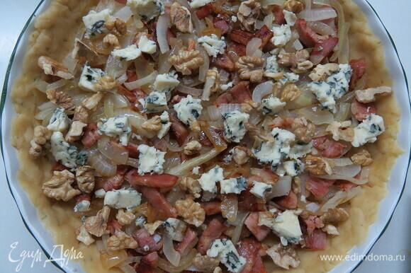 На раскатанное тесто выложить обжаренный лук, кубики ветчины, орехи и кусочки сыра с голубой плесенью (можно также использовать сыр бри).