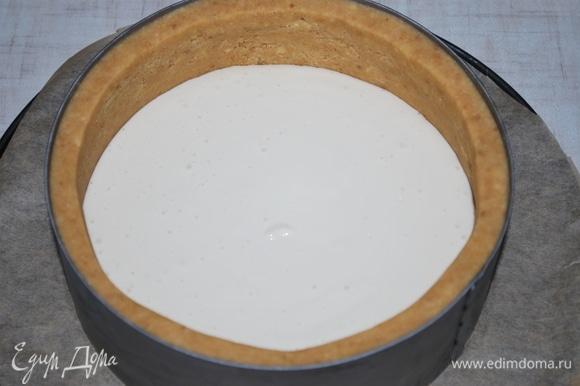 Достаньте из холодильника основу для чизкейка и выложите половину сырного слоя с ароматизированным молоком.