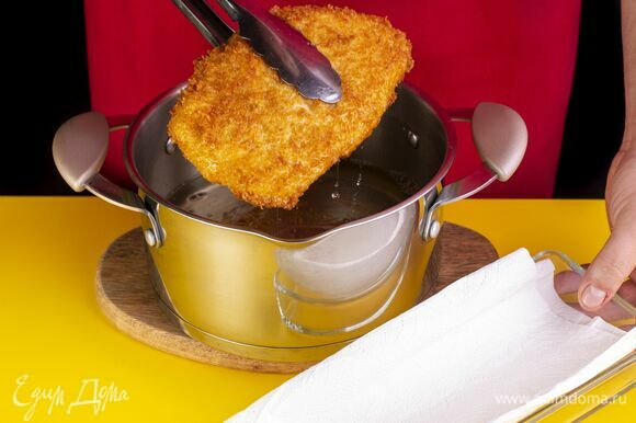 Поставьте на плиту сковороду с высокими бортами или сотейник. Налейте много масла. Опустите один шницель в кипящее масло, затем дождитесь, когда оно закипит повторно, и положите второй шницель. Когда панировка на шницелях как следует прихватится, переверните их.