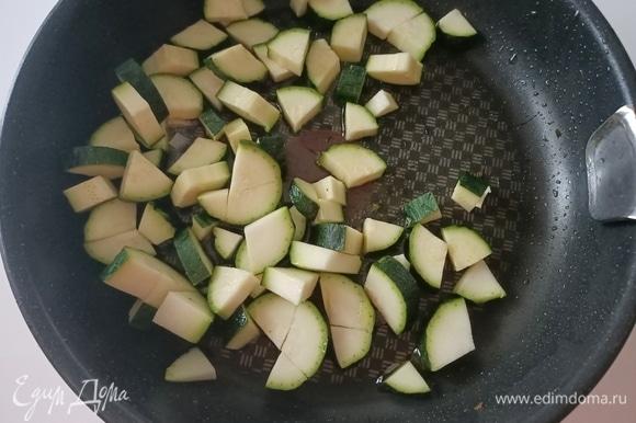 В сковороду налить оливковое масло, добавить чеснок и нарезанный цукини. Посолить, поперчить и жарить 5–7 минут до готовности.