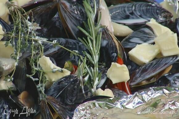 Сделать из нескольких слоев пищевой фольги большую тарелку с бортиками, выложить мидии, полить вином и посолить, затем добавить лук, чеснок и перец чили, веточки тимьяна и розмарина, сверху разложить сливочное масло и полить все сливками.