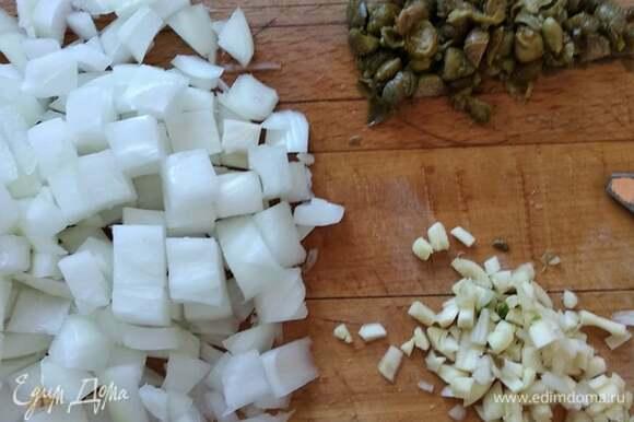 Нарезать мелко лук. Нашинковать чеснок и каперсы. В растительном масле спассеровать лук до прозрачности, добавить чеснок, каперсы и сухой розмарин. Пассеровать еще пару минут.