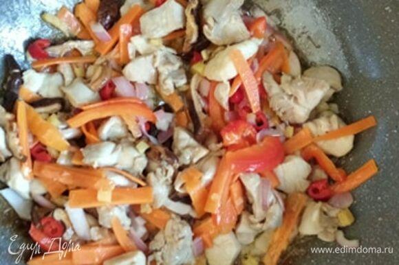 Хорошо прогреть вок или сковороду с толстым дном. Влить растительное масло. Если есть кунжутное, то добавить чайную ложку к базовому маслу. Обжаривать курицу на сильном огне минуты 4. Добавить лук, через минуту — чеснок, чили, имбирь. Еще через минуту — овощи и грибы. Обжаривать все вместе минут 5.