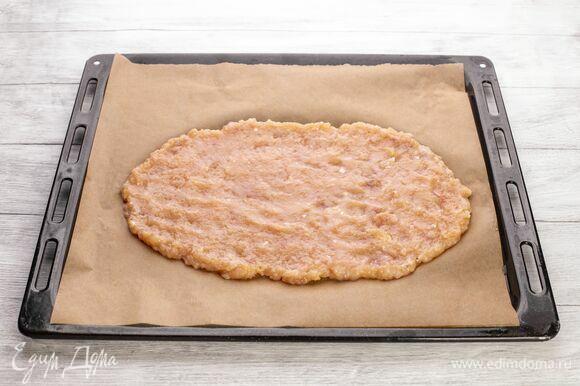 Распределите куриную массу по противню, застеленному пекарской бумагой, в виде тонкой лепешки.
