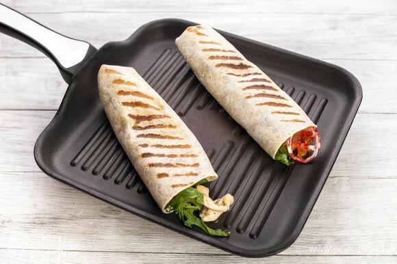 Плотно заверните лаваш с правой стороны. Разрежьте посередине на две части. Обжаривайте на сухой сковороде по 2 минуты с обеих сторон. Все то же самое повторите с оставшейся частью ингредиентов.