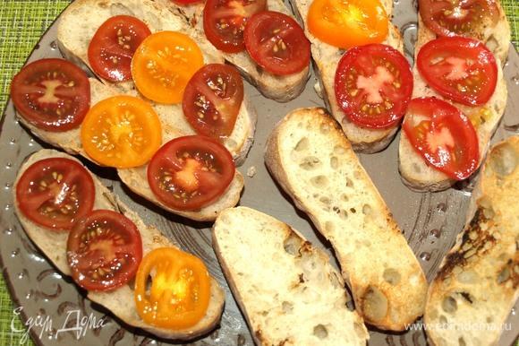 Кладем подсушенный хлеб на блюдо. Выкладываем на хлеб томаты.