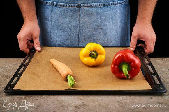 Перцы и морковь целиком выложите на противень, застеленный пергаментной бумагой, и запекайте 20 минут при 210 °C.