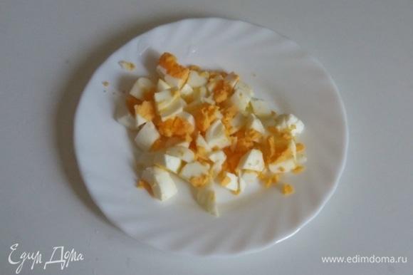 Куриное яйцо сварить вкрутую, охладить, очистить от скорлупы и нарезать мелкими кубиками.