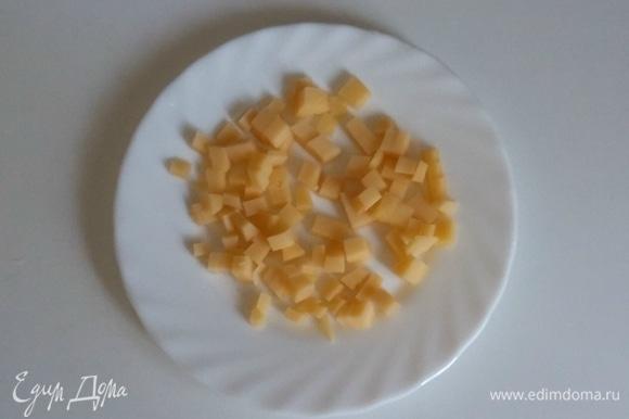 Сыр нарезать пластинками, а затем каждую пластинку нарезать на кубики.