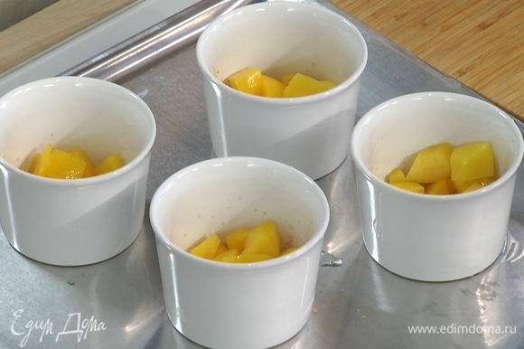 Керамические формочки смазать растительным маслом, дно присыпать коричневым сахаром, разложить в них нарезанные персики и залить тестом.