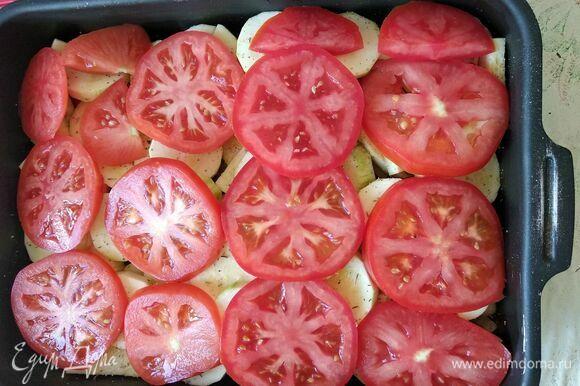 Помидоры нарезать кольцами и выложить поверх кабачков. Разогреть духовку до 200°C. Поместить форму в духовку на 15 минут.
