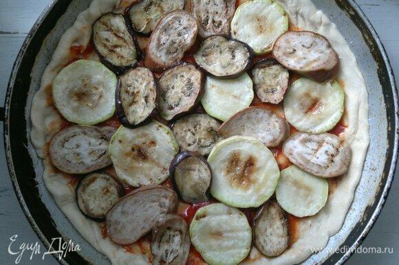 Круг теста смазать томатным соусом, отступая от края 1,5–2 см. Затем выложить обжаренные кружки овощей. Немного посолить и поперчить.