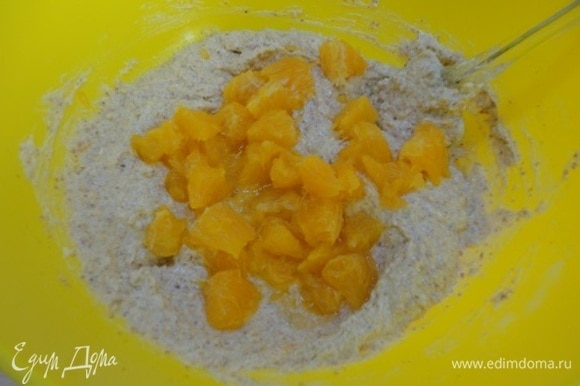 Добавьте половину кусочков апельсина и перемешайте.