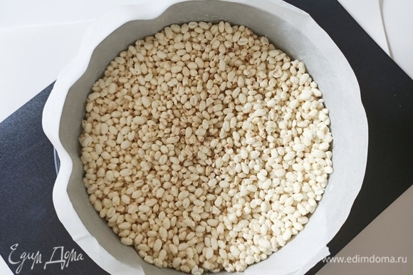 Белый шоколад (150 г) необходимо растопить на водяной бане и смешать с воздушным рисом. Форму для выпечки (22 см) застелить пергаментной бумагой. На дно формы выкладываем рисовые шарики с шоколадом и отправляем форму в холодильник на 30 минут.